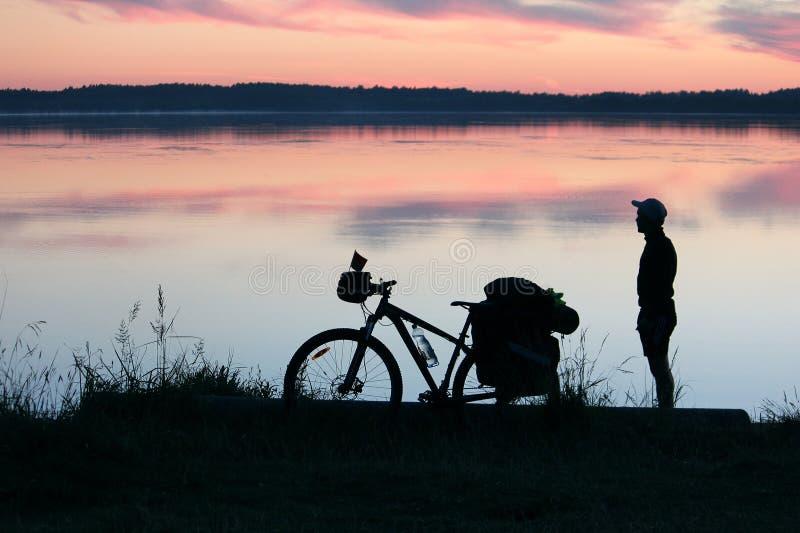Silhueta de um turista e de uma bicicleta fotografia de stock