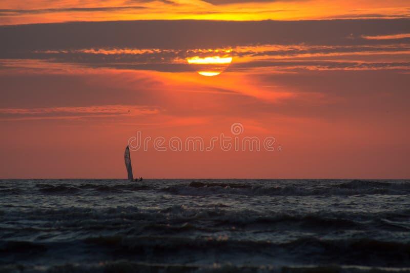 Silhueta de um veleiro no tempo do por do sol imagens de stock royalty free