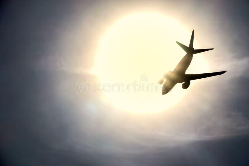 A silhueta de um voo do plano de jato no sol imagem de stock