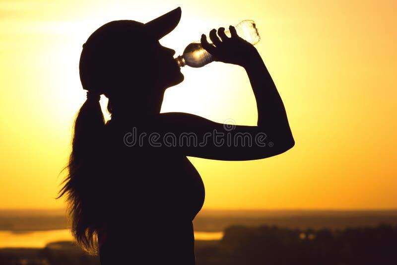 Silhueta de uma água potável da mulher após o exercício físico na natureza, o perfil fêmea dos esportes no por do sol, o conceito fotos de stock