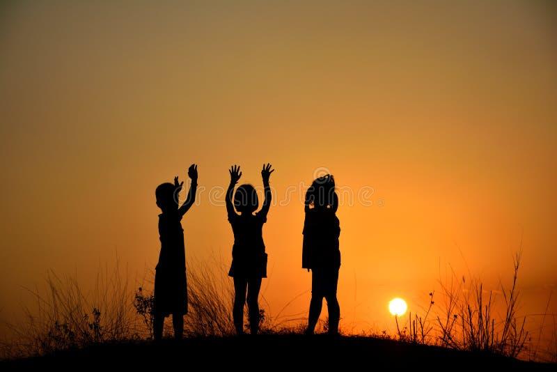 Silhueta de uma amizade de três crianças no por do sol Amigos dos povos fotos de stock royalty free
