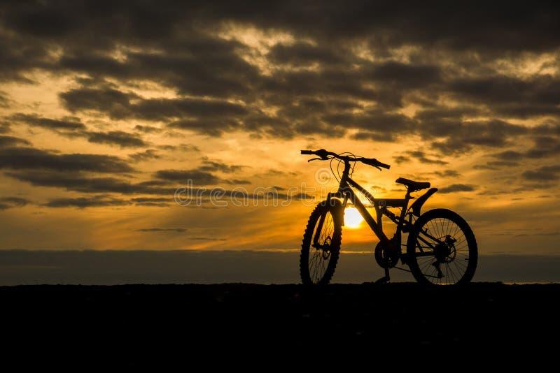 Silhueta de uma bicicleta contra o sol de ajuste imagens de stock royalty free