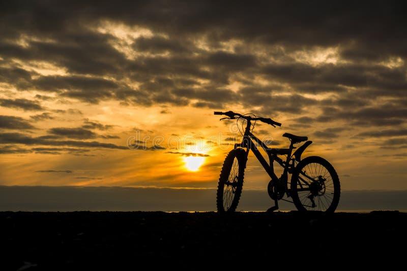 Silhueta de uma bicicleta contra o sol de ajuste fotografia de stock
