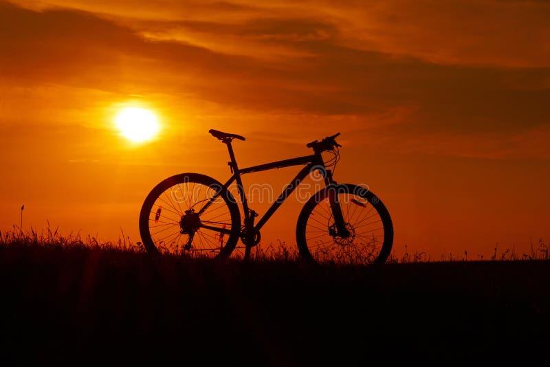 Silhueta de uma bicicleta no fundo do por do sol foto de stock royalty free