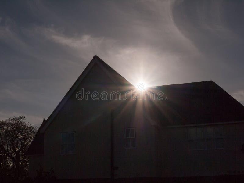 A silhueta de uma casa pointy com um alargamento do sol que repica o throug imagens de stock royalty free