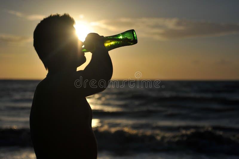 Silhueta de uma cerveja bebendo do homem na praia imagens de stock royalty free