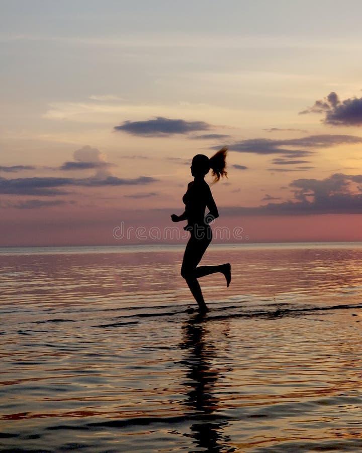 silhueta de uma corrida da menina na areia da praia Tiro contra o sol Por do sol sobre o mar fotografia de stock