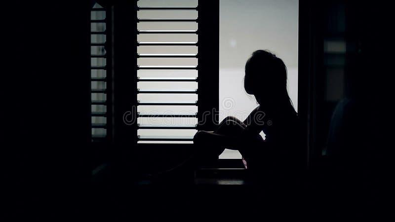 Silhueta de uma criança que se esteja sentando no peitoril e se esteja olhando para fora a janela video estoque