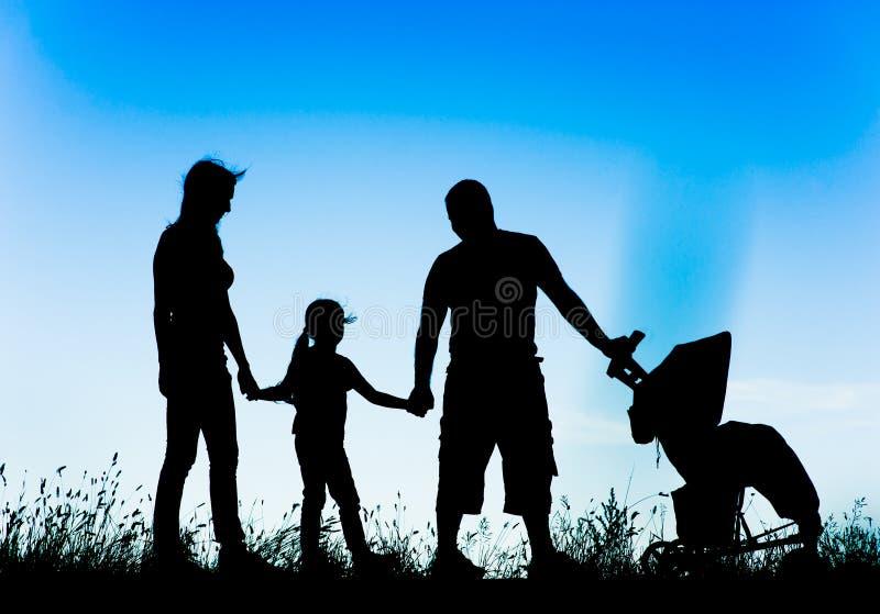Silhueta de uma família feliz que anda com carrinho de criança imagem de stock royalty free