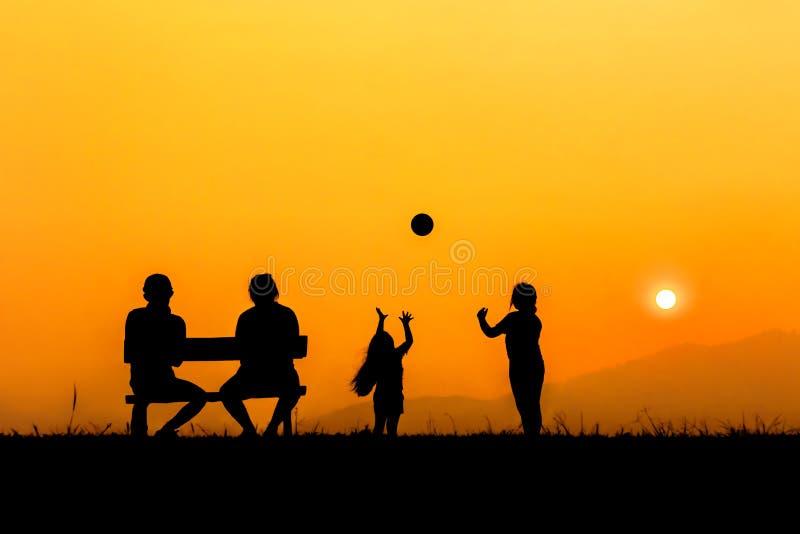 Silhueta de uma família feliz que joga no por do sol foto de stock royalty free