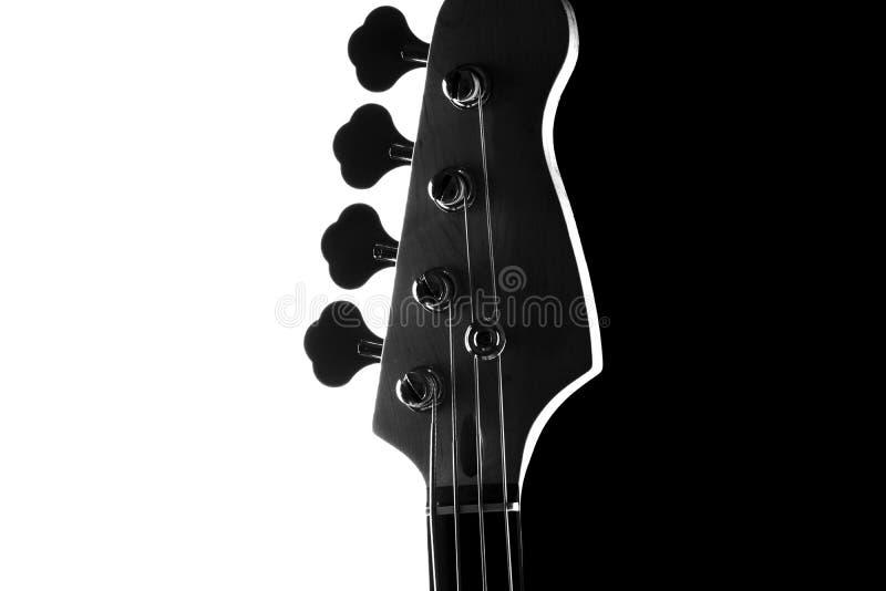 Silhueta de uma guitarra-baixo elétrica em um fundo preto e branco de contraste Fim acima fotografia de stock royalty free