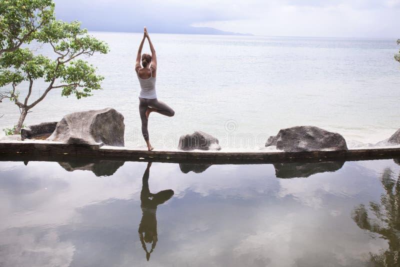 Silhueta de uma ioga praticando da jovem mulher bonita na frente do lago no nascer do sol foto de stock