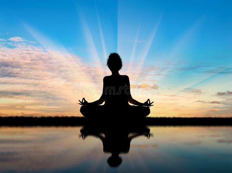 Silhueta de uma ioga praticando da menina foto de stock royalty free
