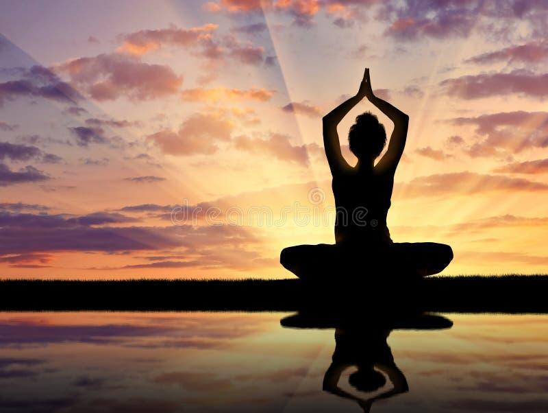 Silhueta de uma ioga praticando da menina imagens de stock royalty free