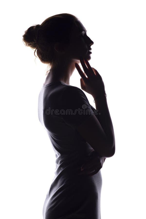 Silhueta de uma jovem mulher calma em um fundo isolado branco, figura da menina pensativa magro fotos de stock royalty free