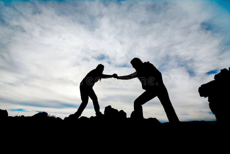 Silhueta de uma mão amiga entre o montanhista dois imagem de stock