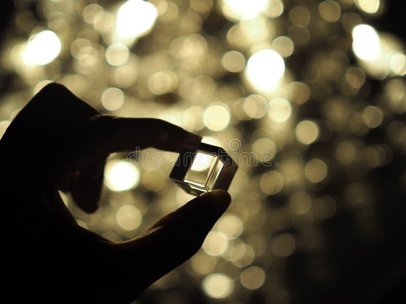 Silhueta de uma mão masculina que guarda um cubo de vidro com fundo do bokeh Foco selecionado