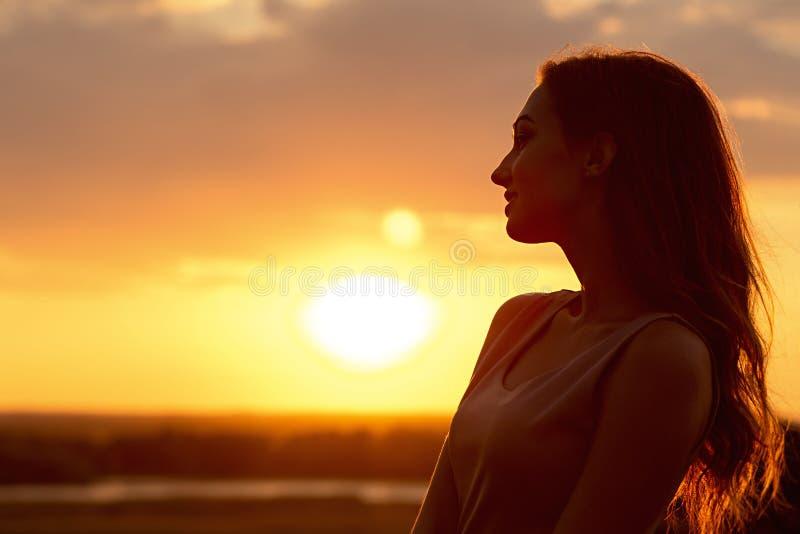 Silhueta de uma menina bonita no por do sol em um campo, perfil da cara da jovem mulher que aprecia a natureza fotografia de stock