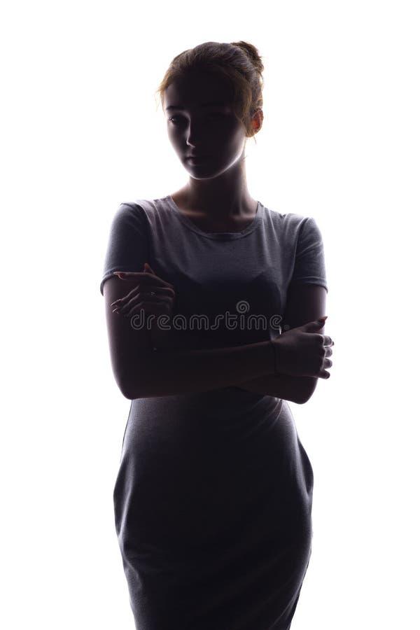 Silhueta de uma menina bonita que olha seguramente para a frente, figura da jovem mulher em um fundo isolado branco fotos de stock