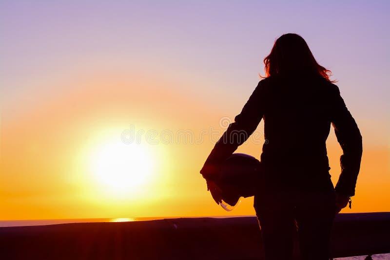 Silhueta de uma menina do motociclista no por do sol imagens de stock royalty free