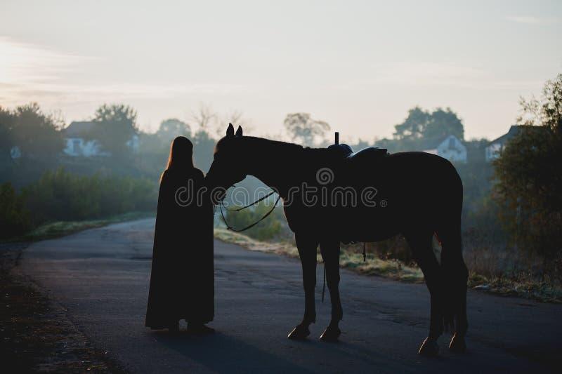 Silhueta de uma menina em uma capa de chuva que beija um cavalo no fundo escuro com névoa azul fotografia de stock royalty free