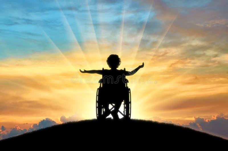 Silhueta de uma menina feliz da criança deficiente que senta-se em uma cadeira de rodas sobre um monte no por do sol fotos de stock
