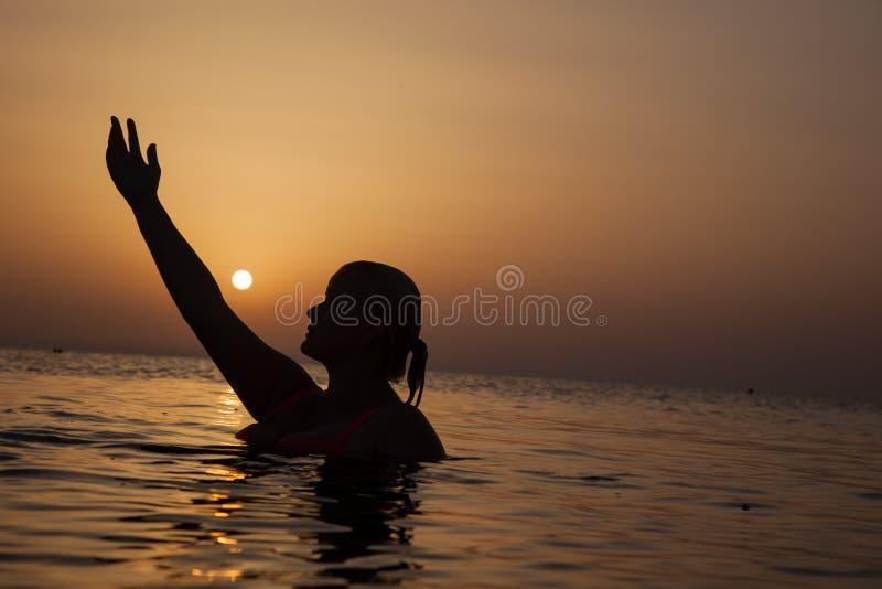 Silhueta de uma menina no oceano no por do sol, mulher do oceano no nascer do sol l imagem de stock royalty free