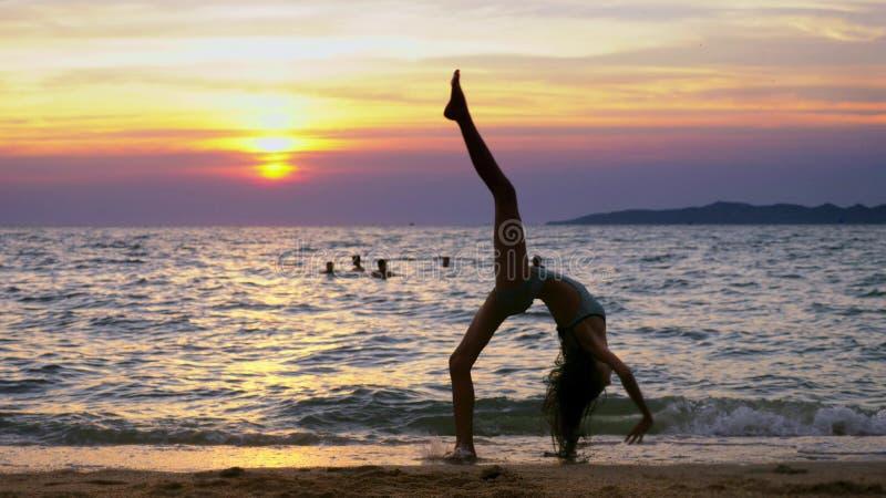 Silhueta de uma menina no por do sol, na perspectiva do mar, golpe ginásticos fazendo engraçados da menina pernudo delgada no foto de stock royalty free