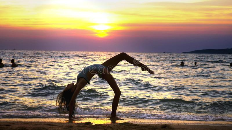 Silhueta de uma menina no por do sol, na perspectiva do mar, golpe ginásticos fazendo engraçados da menina pernudo delgada no imagem de stock