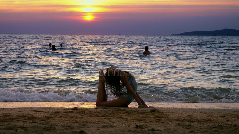 Silhueta de uma menina no por do sol, na perspectiva do mar, golpe ginásticos fazendo engraçados da menina pernudo delgada no fotos de stock