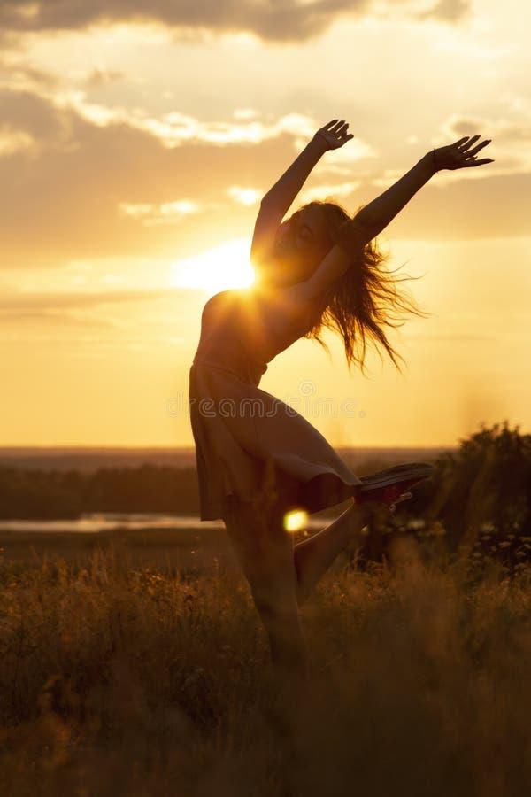 Silhueta de uma menina sonhadora bonita no por do sol em um campo, um idance da jovem mulher com felicidade na natureza fotografia de stock