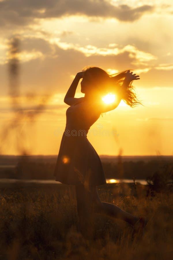 Silhueta de uma menina sonhadora bonita no por do sol em um campo, um idance da jovem mulher com felicidade na natureza foto de stock royalty free
