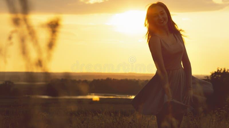 Silhueta de uma menina sonhadora em um campo no por do sol, uma jovem mulher que aprecia a natureza imagens de stock royalty free