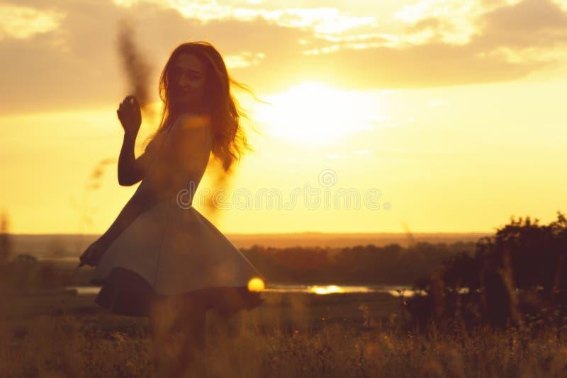 Silhueta de uma menina sonhadora em um campo no por do sol, uma jovem mulher que aprecia a natureza fotos de stock royalty free