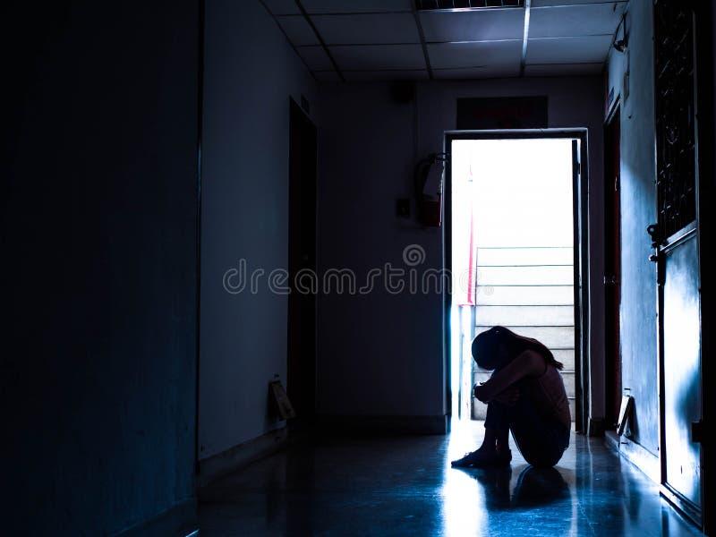 Silhueta de uma moça triste que senta-se na obscuridade, pensando sobre o problema com relacionamentos ou trabalho, desespero de  fotos de stock