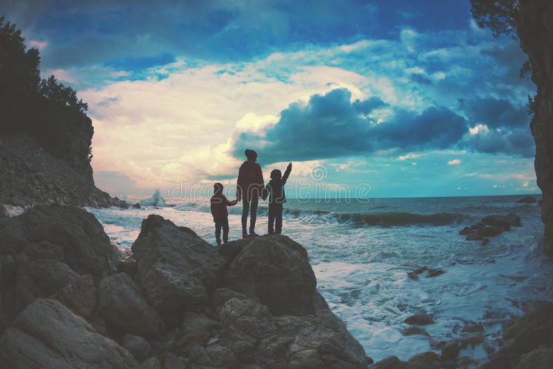 Silhueta de uma mulher e crianças contra o mar e o céu imagens de stock royalty free