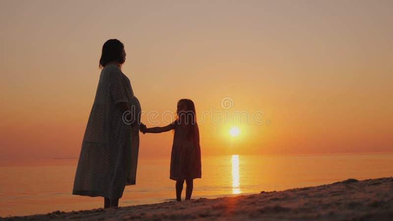 Silhueta de uma mulher gravida com um bebê próximo perto Suporte perto do mar no por do sol Esperando a segunda mudança imagem de stock