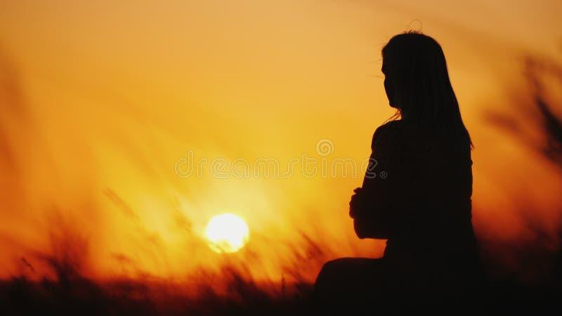 Silhueta de uma mulher na grama alta no por do sol Grama que balan? no vento fotos de stock