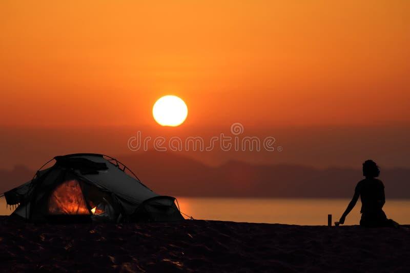 Silhueta de uma mulher que acampa com as barracas na praia fotos de stock royalty free