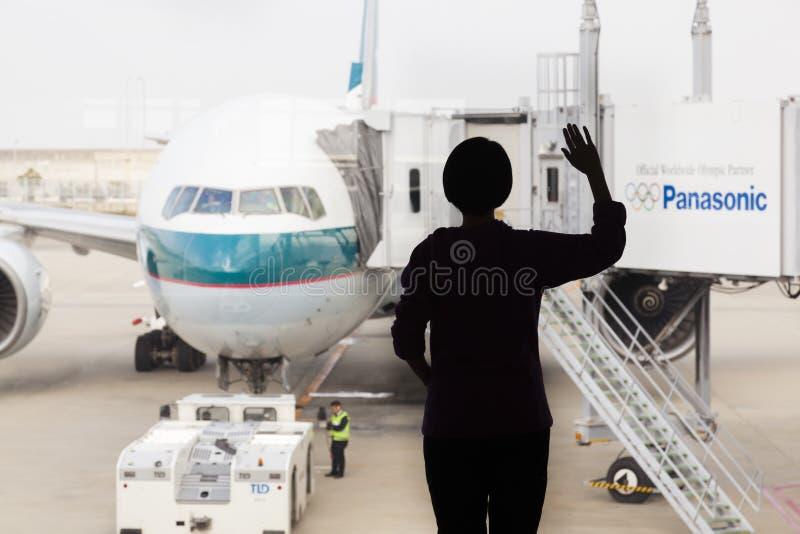 Silhueta de uma mulher que acena adeus a um avião fotografia de stock
