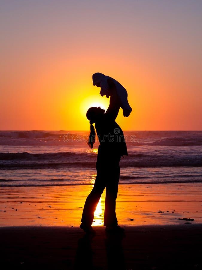 Silhueta de uma mulher que guarda um bebê acima de alto em uma praia no por do sol fotografia de stock royalty free