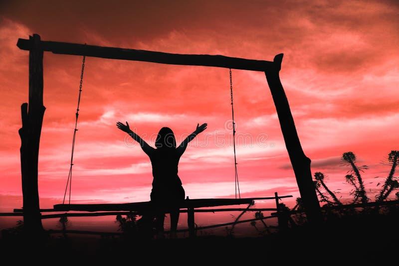 Silhueta de uma mulher que tem o divertimento que senta-se no balanço no pôr do sol com as nuvens bonitas no fundo, na liberdade  fotos de stock