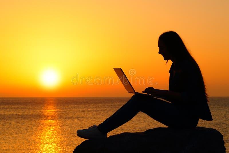 Silhueta de uma mulher que usa o portátil no por do sol imagem de stock royalty free
