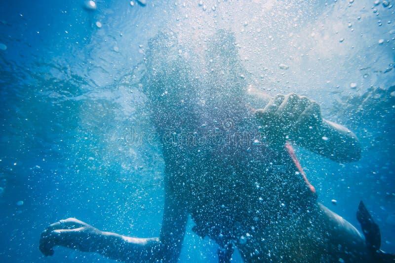Silhueta de uma mulher sob a água Fundo fotografia de stock