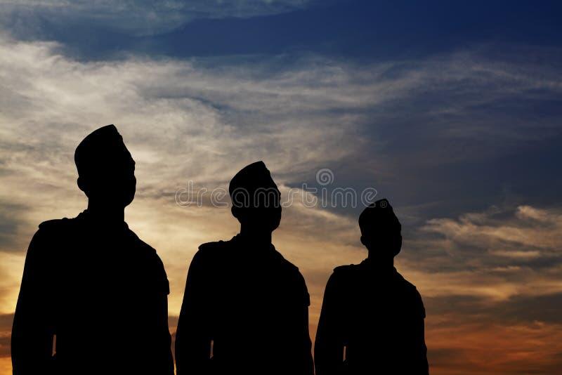 Silhueta de uma parada de três homens. imagens de stock