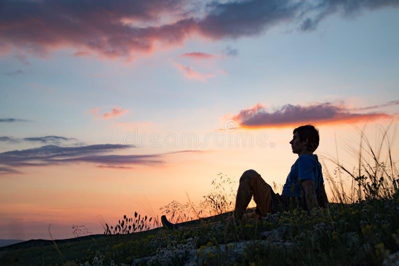 Silhueta de uma pessoa de encontro ao por do sol foto de stock