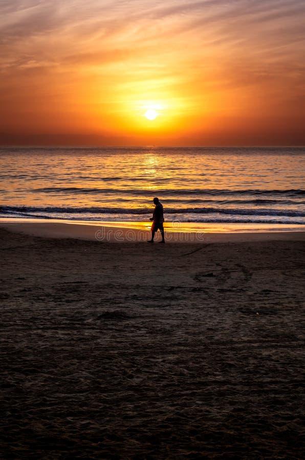 Silhueta de uma pessoa que anda o na praia imagens de stock