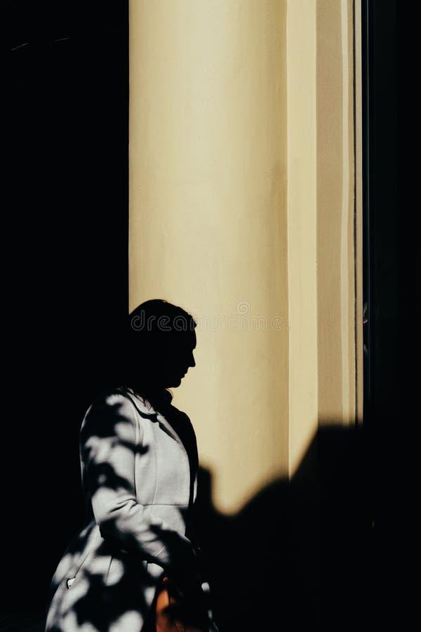 Silhueta de uma posi??o da pessoa nas sombras imagem de stock