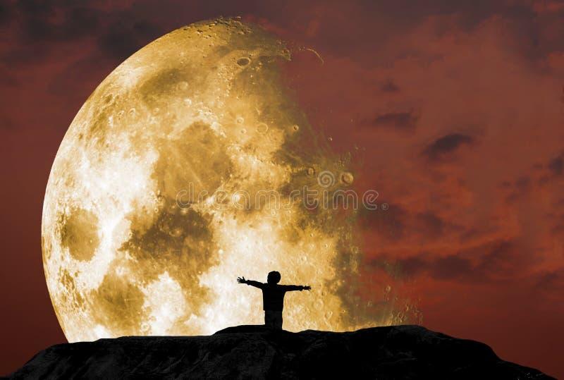 Silhueta de uma posição do menino com seus braços estendidos felizmente, em um penhasco rochoso de inclinação com um céu crepuscu foto de stock royalty free