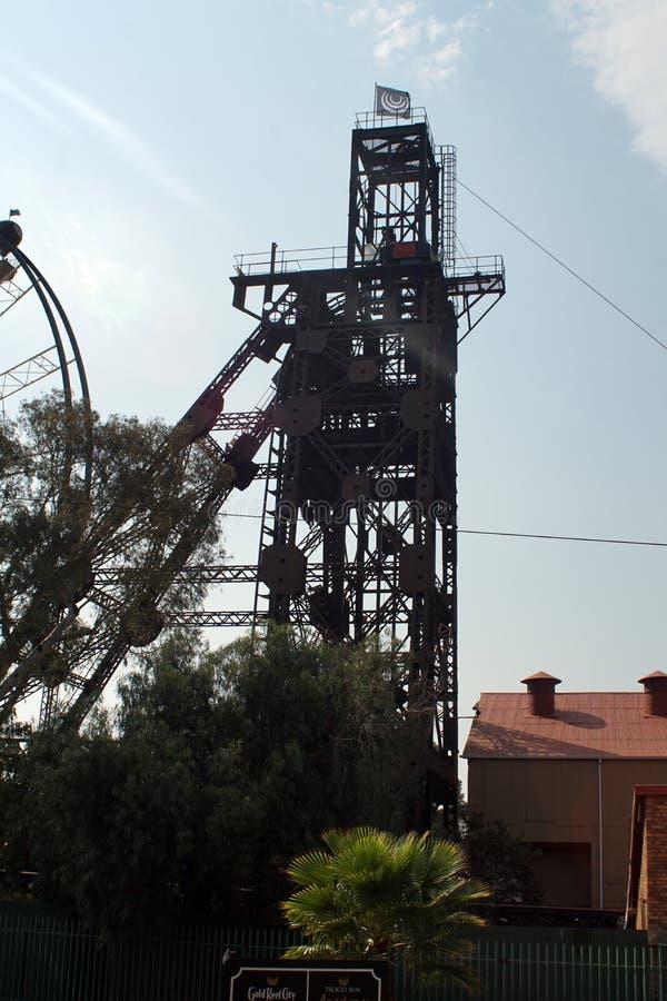A silhueta de uma roda de ferris e a mina velha dirigem foto de stock royalty free
